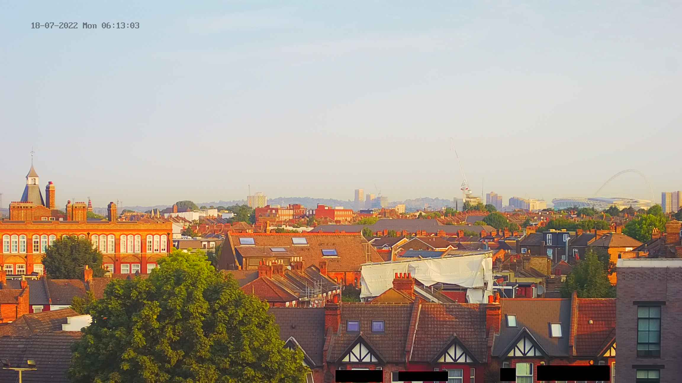 Image from a webcam showing a view of north-west London, with Wembley Stadium on the horizon on the right, and a spire on a school on the left. Houses from streets in Kensal Green are visible in the foreground.